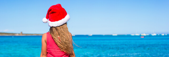 Cute little girl in Santa hat on the beach during vacation