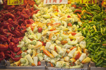 Peppers in row at a farmers market . Red yellow green paprika