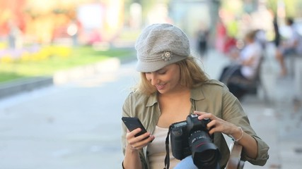 Trendy young photographer with camera and smartphone