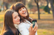 Two teenage girls taking selfies in the park on sunny autumn day