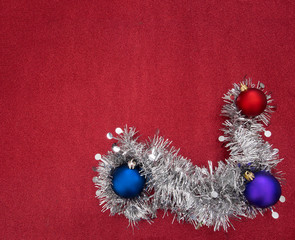 Silver tinsel garland and Christmas baubles on red glitter festi
