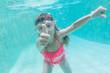 child girl swimming underwater in mask