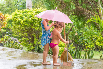 two child girls cleaning up the path, outdoors, during the rain