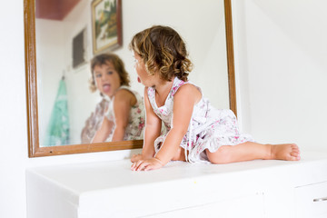 young beautiful child girl looking at herself in mirror at home