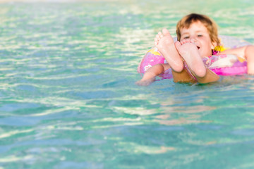 young happy child swimming in the sea in a floating ring on trop