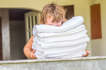young cute child girl holding rolled beach or spa towels on outd