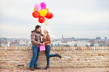 Happy couple with colorful balloons outdoors