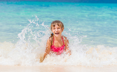 young happy child girl having fun in water, tropical summer vaca