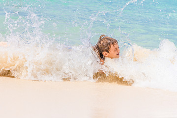 young happy child boy having fun in water, tropical summer vacat