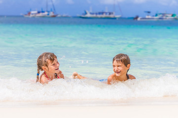 two young happy children - girl and boy - having fun in water, t