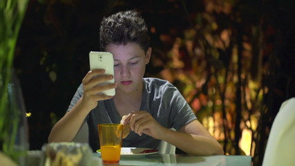 Young teenager eating sandwich and using  smartphone at home at
