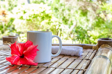 white mug with cappuchino on bamboo table, coffee cup in the mor