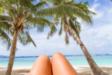 woman's legs on tropical beach and sea background, summer vacati