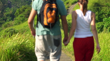 Couple holding hands on trip and walking through terraces in Bal