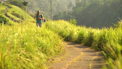 Handsome man on trip, walking ad hiking through terraces in Bali