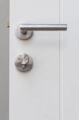 Aluminium door knob on the white door