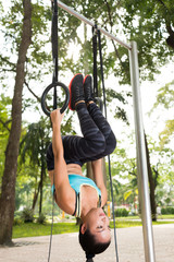 Sporty woman hanging on gymnastic rings upside down