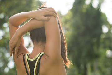 Rear view of woman stretching her arm and shoulder
