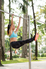 Fit woman raising her straight legs hanging on gym bar