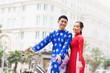 Portrait of beautiful Vietnamese couple posing on bicycle