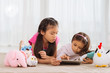 Little girls playing with knitted toys and digital tablet