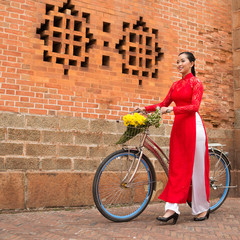 Young Vietnamese woman walking with a bicycle