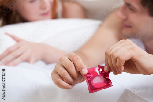Male hands opening condom