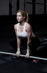 Fitness woman lifting barbell