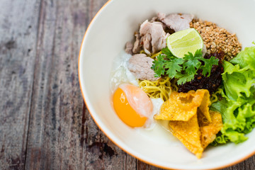Pork noodle with Soft-boiled egg on wooden table