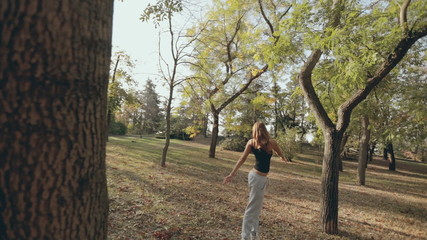 Girl does sports exercises in a park where the leaves fall