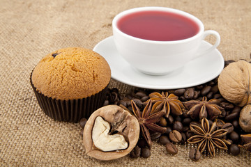 cakes, grains of coffee, seasonings and cup of floral tea
