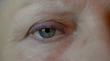 Close-up of blue female eye looking at camera.