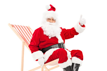 Santa giving a thumb up seated in a sun lounger