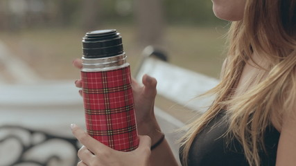 The girl opens the thermos and pours tea in the park