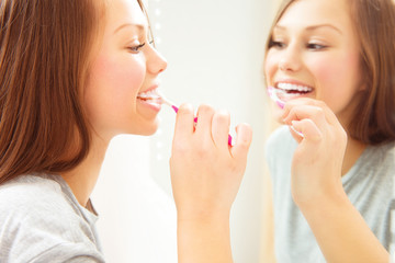 Pretty young woman brushing her teeth. Dental hygiene