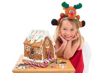 Festive little girl making gingerbread house
