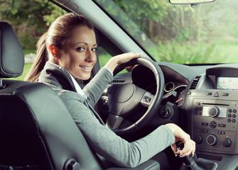 Smiling woman driving and looking at camera