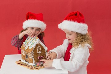 Festive little girls making a gingerbread house