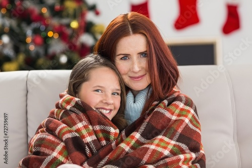 canvas print picture Festive mother and daughter wrapped in blanket