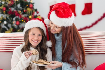 Festive mother and daughter on the couch with cookies