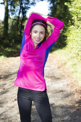 Fitness woman stretching in forest in autumn