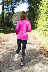 Woman jogger outside in forest
