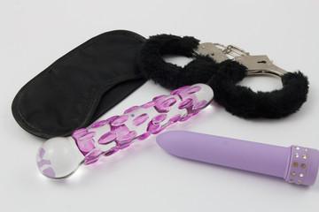 Sex Toys - Maske, Handschellen, lila Vibrator und Glas Dildo