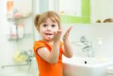 Fototapety Cute little girl washing hands in bathroom