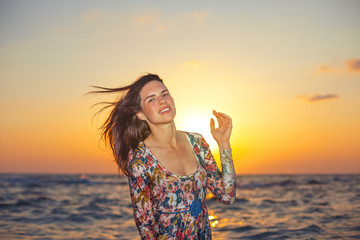 beautiful girl shaking long hair in sunset
