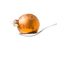 yellow xmas ball in the spoon - isolated