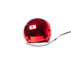 red xmas ball in the spoon - isolated