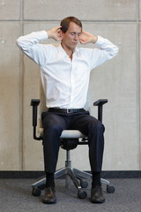 business man exercising on chair - yoga office