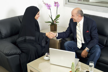 Senior Businessman Shaking hands with Woman wearing hijab