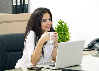 Young pretty business woman having coffee in office